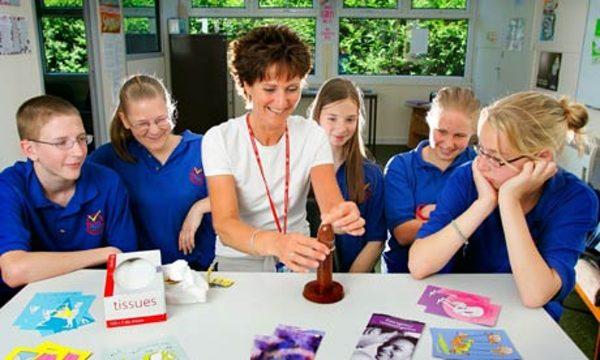 Cô giáo hướng dẫn học sinh sử dụng bao cao su trong một tiết học về giáo dục giới tính. Ảnh: The Guardian